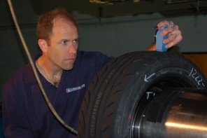 Dave Kaemmer takes measurements of a racing tire for research purposes