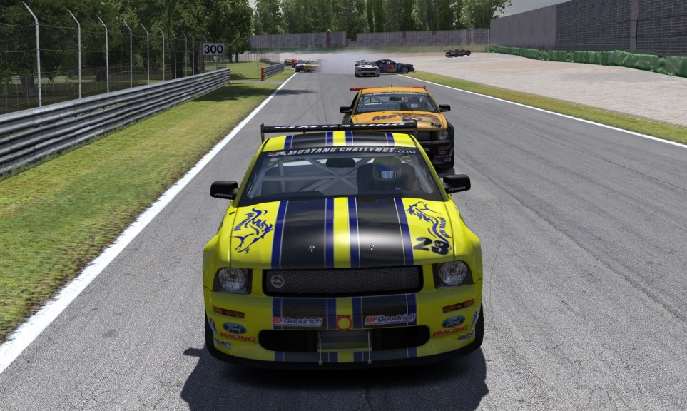 Smoke and mayhem break out behind race leader Liam Hackwith (#23) and Tyler Shifflett (#13) on the opening lap at Monza.